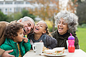Grandparents and grandchildren laughing, eating lunch