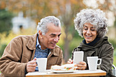 Senior couple with smart phone, eating lunch