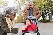 Grandparents feeding grandson in stroller at park