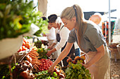 Woman working, arranging produce at farmer's market
