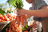 Woman holding bunch of carrots at farmer's market