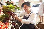 Woman arranging produce at farmer's market