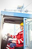 Dock worker driving forklift at shipyard