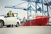 Dock manager using walkie-talkie outside car at shipyard