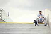 Businessman using digital tablet on urban steps