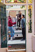 Friends laughing at back of moving van