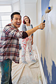 Portrait happy couple painting wall