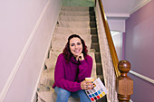 Woman redecorating, holding paint swatch on stairs