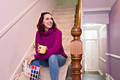 Woman with paint swatches redecorating on stairs