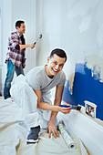 Portrait happy man painting wall