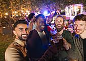 Portrait happy male friends drinking at garden party