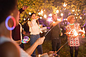 Friends with sparklers enjoying garden party