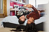 Happy teenage girls taking selfie upside-down on bed
