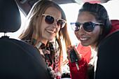 Portrait happy young women wearing sunglasses in car