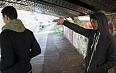 Menacing man gesturing finger gun at man in urban tunnel