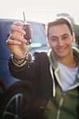 Man holding new car keys with heart-shape key chain