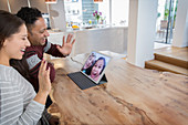 Happy parents video conferencing with daughters