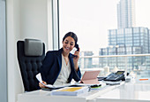 Smiling businesswoman talking on telephone in urban office