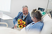 Senior man with flower bouquet visiting wife in hospital
