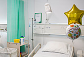 Get Well balloons tied to bed in vacant hospital room