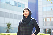 Portrait young woman wearing hijab outside sunny building
