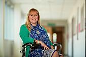 Portrait woman in wheelchair in corridor
