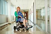 Woman wearing medical boot in wheelchair in corridor