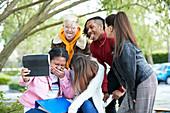 Playful college student friends digital tablet selfie park
