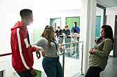 College students talking and laughing in corridor