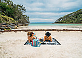 Couple sunbathing on remote tropical ocean beach