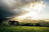 Sunrise clouds over idyllic rural green landscape