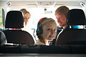 Portrait girl with headphones riding in back seat of car
