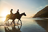 Young women horseback riding in sunny sunset ocean surf