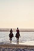 Young women horseback riding in ocean surf
