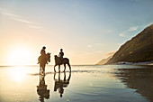 Women horseback riding in tranquil ocean surf at sunset