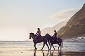 Young women horseback riding on tranquil ocean beach