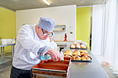 Focused man with Down Syndrome baking bread in kitchen