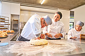 Chef guiding student with Down Syndrome kneading dough
