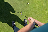 Point of view man putting golf ball on sunny greens