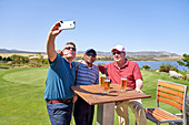 Male friends drinking beer and taking selfie