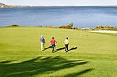 Male golfers walking toward pin