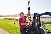 Male golfer choosing golf club at tee box