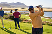 Mature male golfer teeing off at sunny box