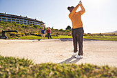 Male golfer taking a shot out of sunny bunker
