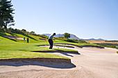 Male golfer taking a shot above sunny sand trap
