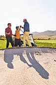Male golfers celebrating behind sunny golf bunker