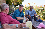 Mature golfer friends talking and drinking water on patio