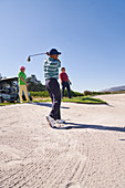 Male golfer taking a shot out of sunny golf bunker