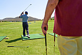 Male golfer practicing at sunny golf course driving range