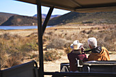 Senior couple on safari looking at view outside vehicle